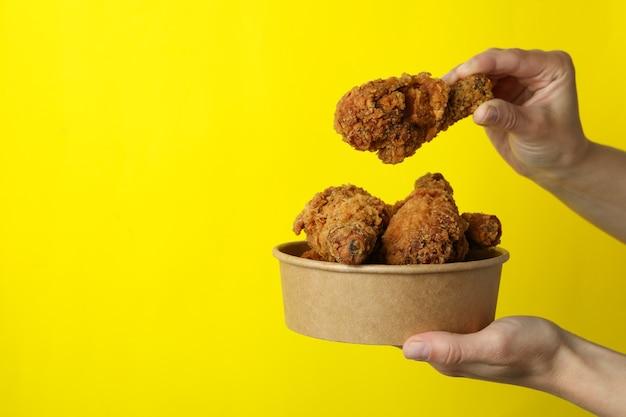 여성의 손을 잡고 노란색 바탕에 프라이드 치킨