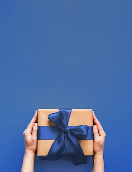 Female hands hold gift box on deep blue background