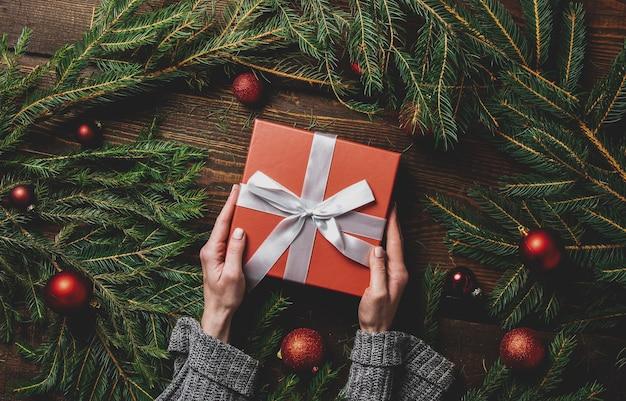 Женские руки держат подарочную коробку рядом с рождественским украшением на столе