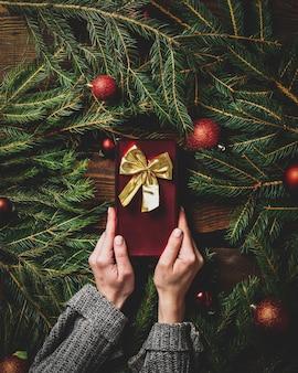 Женские руки держат подарочную коробку рядом с ветками елки и безделушками вокруг