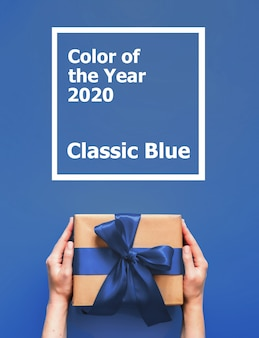 Female hands hold gift box with words color of the year 2020 classic blue.