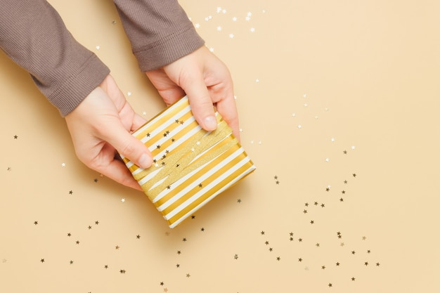 Female hands hold gift box wrapped in golden paper with golden confetti stars