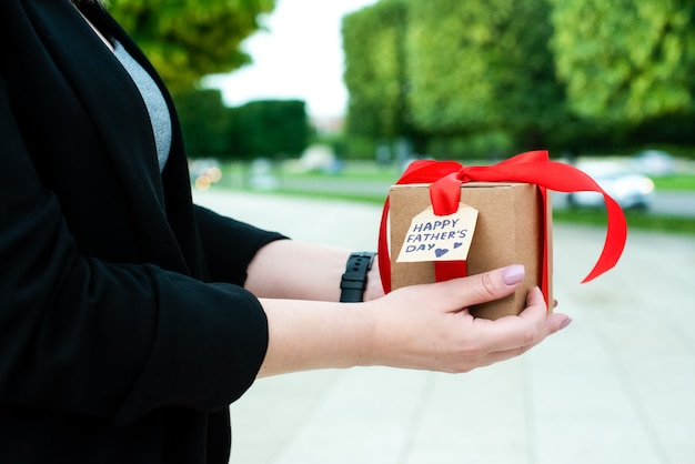 Female hands hold a gift for dad on father's day. in a craft box, with a red ribbon and a tag. close-up. outside. beautiful morning city nature. holiday concept.