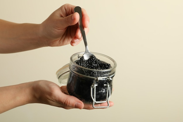 Female hands hold glass jar and spoon with black caviar