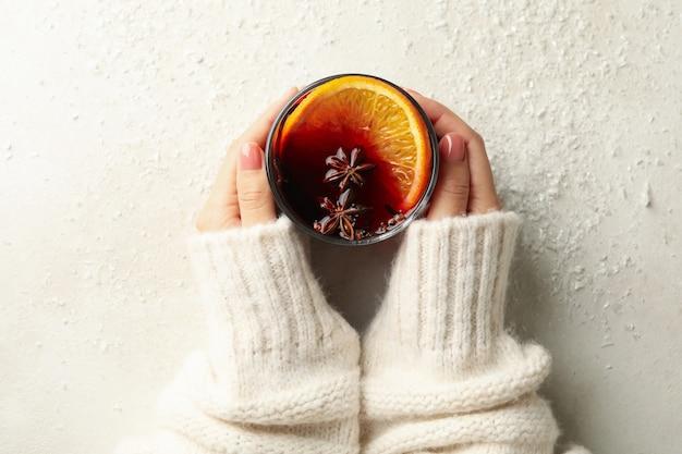 女性の手はグリューワインのガラスを保持します