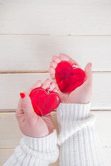 Female hands hold a glass red heart. valentine's day greeting card. care and health concept, healthcare, heart health theme top view copy space