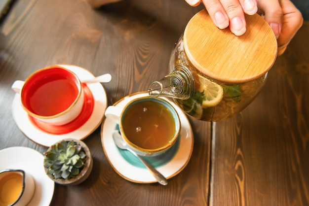 Female hands hold glass teapot, pour tea into mug. wooden table in cafe is served for two for tea, top view.