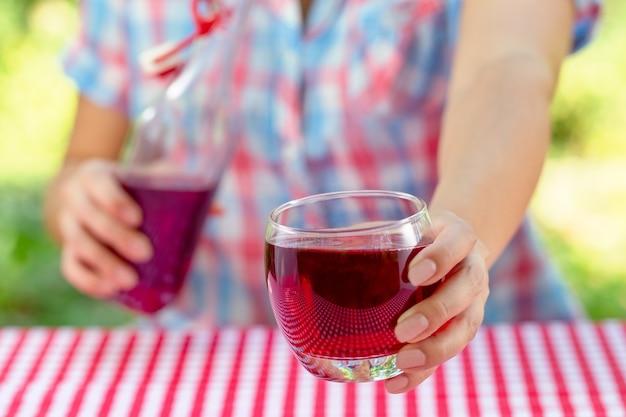 女性の手はブドウや他の赤いジュースとガラスを保持します