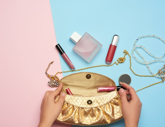 Female hands hold a golden clutch bag with various cosmetics and jewelry on a blue background