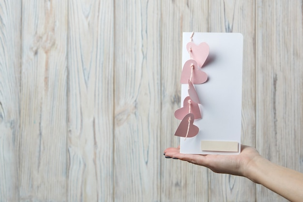 女性の手はピンクのハートで飾られたバレンタインデーのグリーティングカードを保持します。