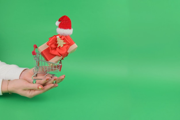 Female hands hold grocery trolley shopping cart with gift wearing santa hat in on a green festive background