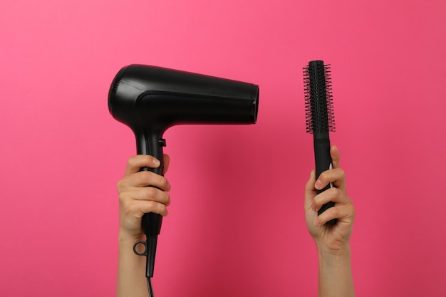 Female hands hold hair dryer and hair brush on pink