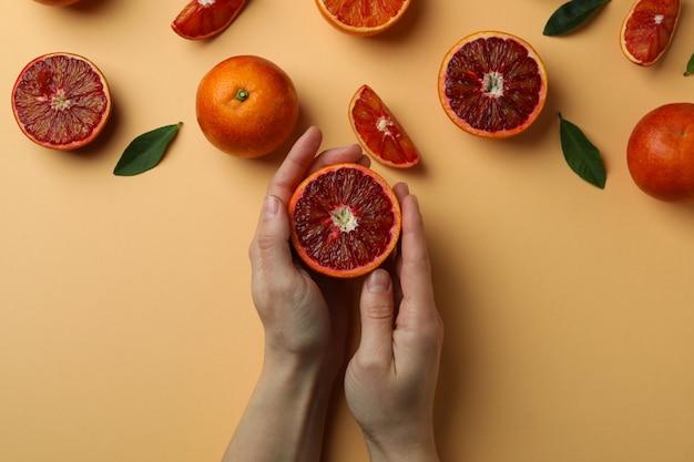 Женские руки держат половину красного апельсина на бежевом с красными апельсинами