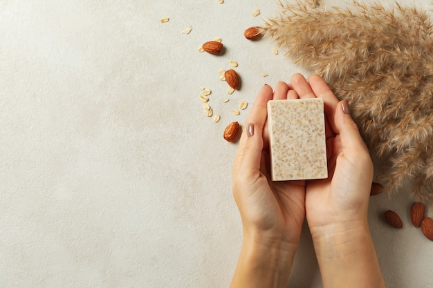 Female hands hold handmade soap on decorated background