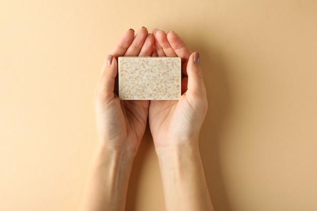 女性の手はベージュの背景に手作り石鹸を保持します