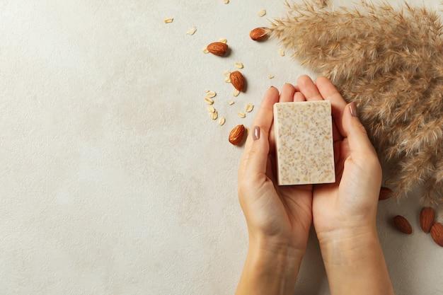 女性の手は装飾された背景に手作り石鹸を保持します