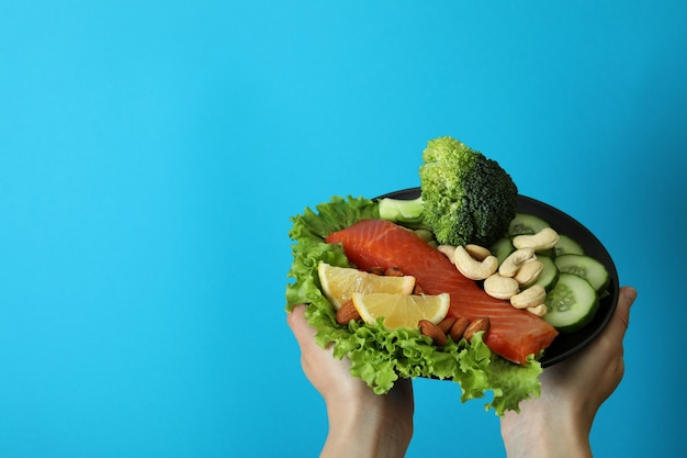 Female hands hold healthy food on blue background