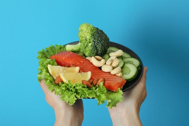 여성의 손을 잡고 파란색 배경에 건강 식품