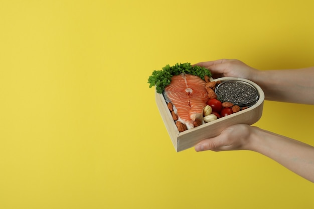 여성 손 노란색 바탕에 건강 식품을 개최