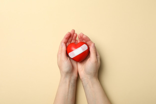 Female hands hold heart with adhesive plaster on beige space, top view