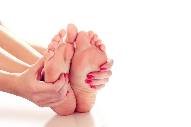 彼女は関節痛があるので、女性の手は彼女の足を保持します