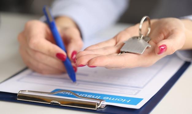 여성의 손에 집 열쇠를 잡고 부동산 보험을 작성합니다. 재산 보험 개념