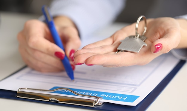 Female hands hold house keys and fill out real estate insurance. property insurance concept