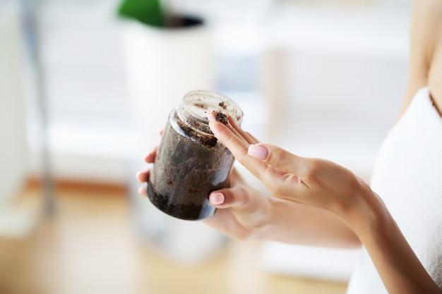 Female hands hold a jar of coffee scrub.