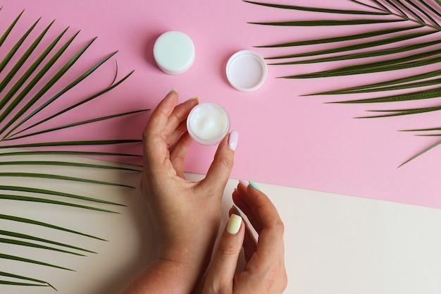 女性の手はパステルピンクとベージュのテーブルの美しさと化粧品のコンセプトにボディクリームの瓶を保持します