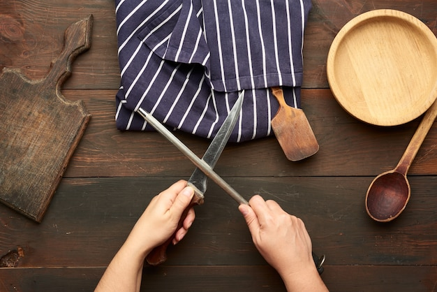 Female hands hold a kitchen knife and a sharpener with a handle