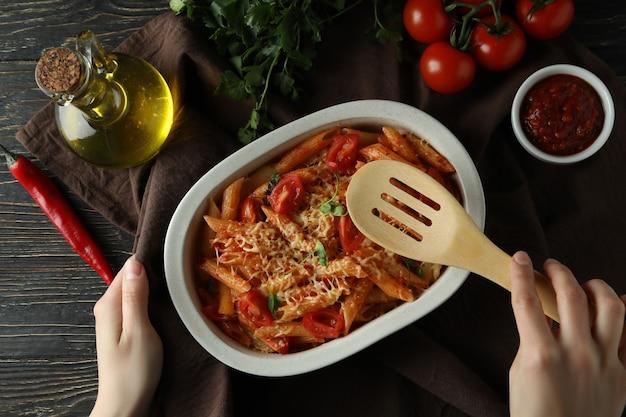 女性の手は、トマトソースのパスタでトレイの上にキッチンヘラを保持します
