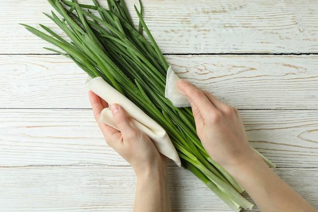 Женские руки держат кухонное полотенце с зеленым луком на белом деревянном