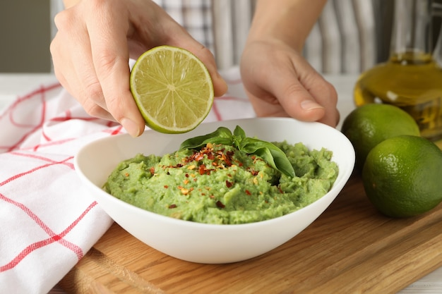 Female hands hold lime and bowl with guacamole