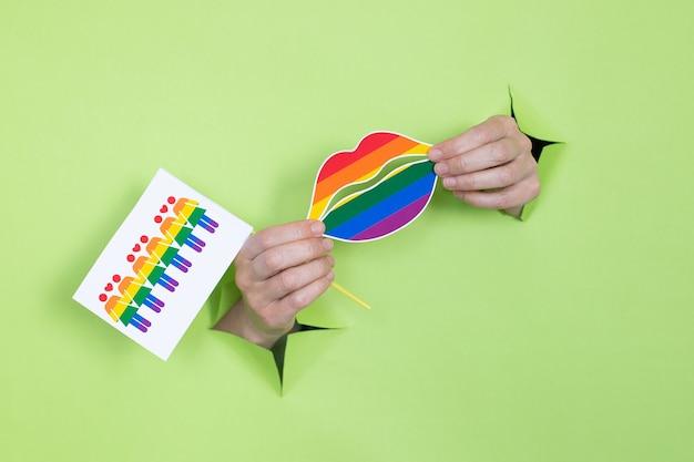 Женские руки держат губы и флаги в цветах радуги на зеленом фоне. концепция лгбт. место для рекламы.