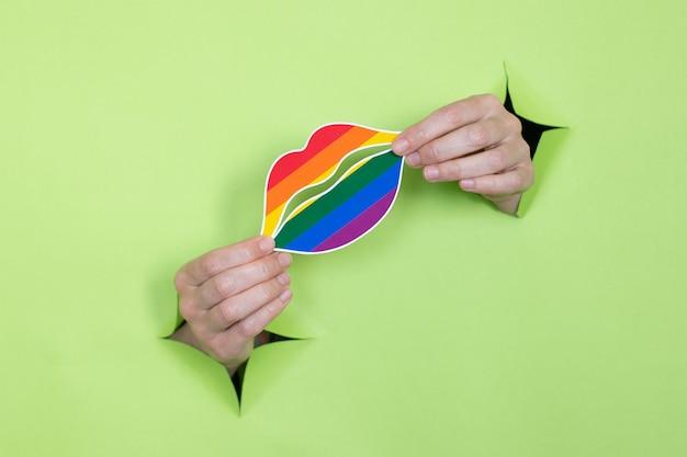 Женские руки держат губы в цветах радуги на зеленом фоне. концепция лгбт. место для рекламы.