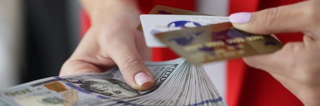 女性の手はたくさんのドル紙幣と銀行のプラスチックカードのクローズアップを保持します