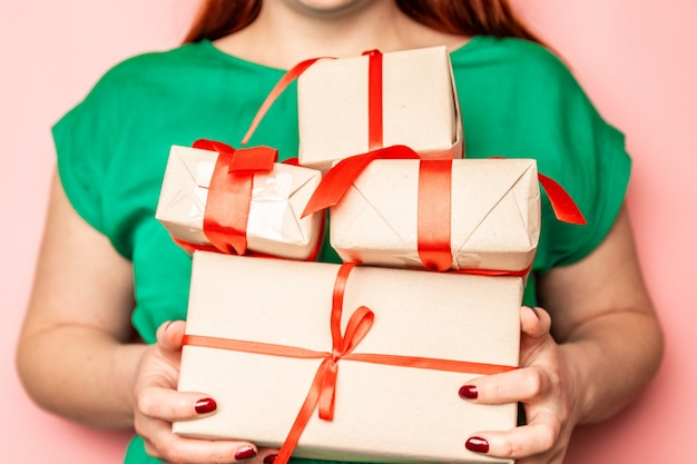 Female hands hold a lot of surprise gift boxes with red ribbons bows