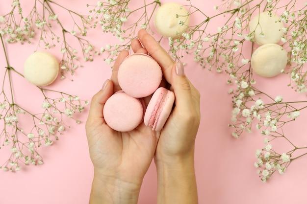 Женские руки держат миндальное печенье на розовом фоне с миндальным печеньем и цветами