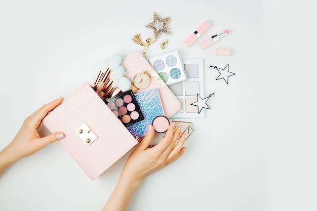 女性の手は化粧品の美容製品で化粧バッグを保持します