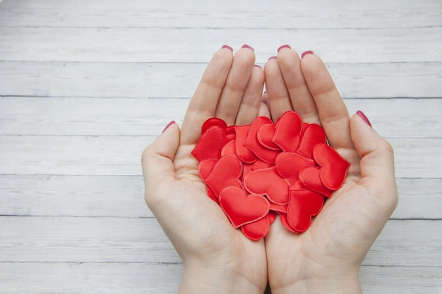 Female hands hold many red hearts in the palm on a wood background, concept of saving love