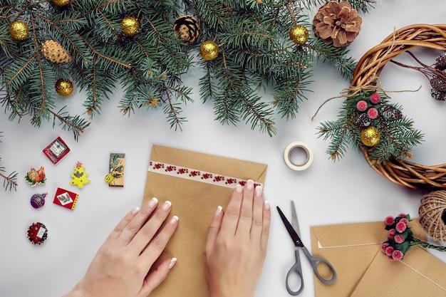 Женские руки держат счастливую рождественскую открытку и конверт рождественские украшения фон плоская планировка вид сверху