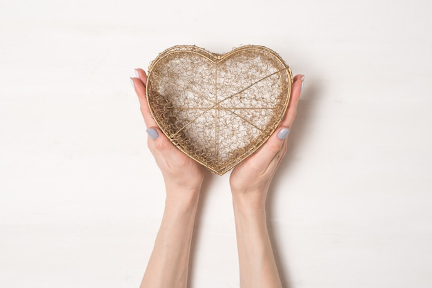 Female hands hold metal wire transparent box in the shape of a heart isolate