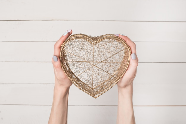 Female hands hold metal wire transparent heart shaped box