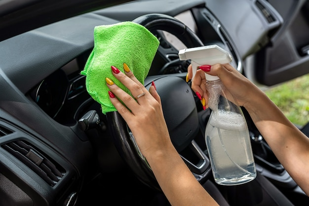 Female hands hold microfiber cloth and spray bottle for cleaning car inside, close up