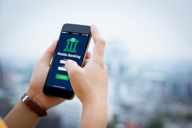 Female hands hold mobile banking on smart phone on blurred urban city