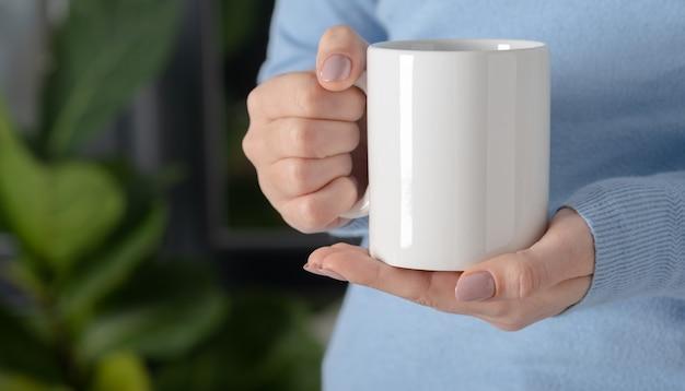 女性の手はあなたのデザインとロゴのクローズアップのための白い空のマグカップ、カップをモックアップします。