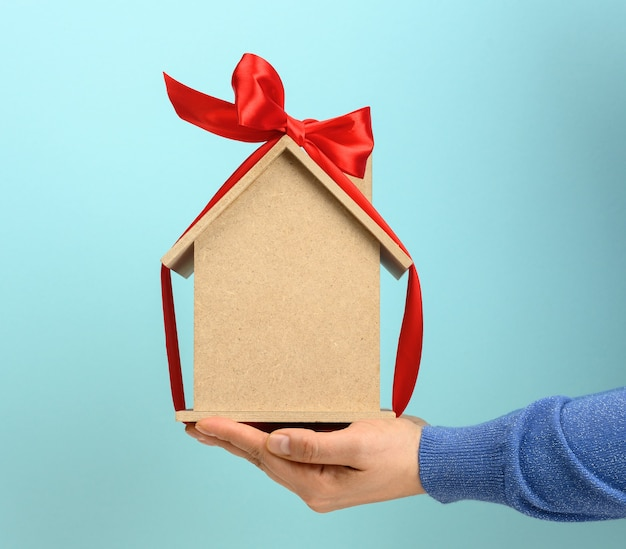 Female hands hold a model of a wooden house tied with a red silk ribbon on a blue background, the concept of real estate purchase, mortgage