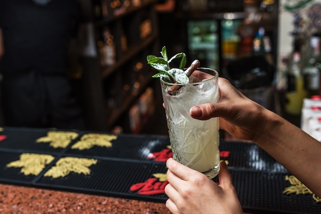 Female hands hold mojito cocktail in a bar