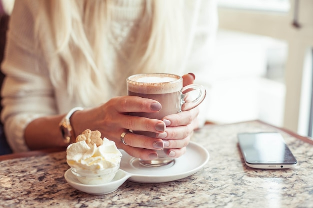 Female hands hold a mug of hot cocoa. a young woman is sitting in a cozy cafe. the girl is drinking cocoa. winter. cozy autumn.
