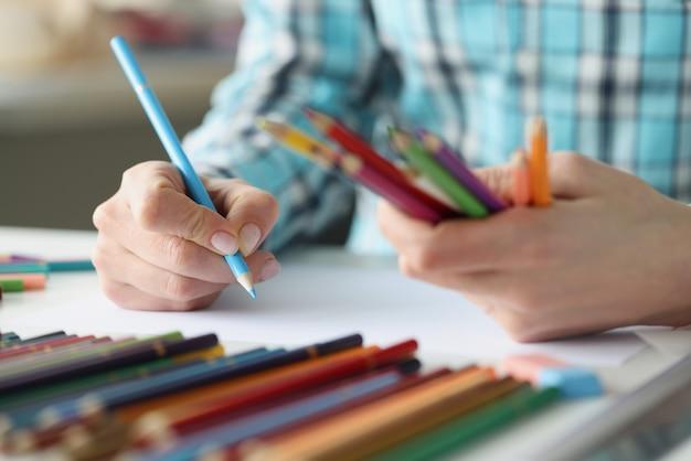 Женские руки держат разноцветные карандаши, а лист бумаги лежит на столе